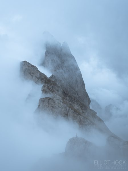 A figure stodd amongst the cloud looking up at Seceda, Dolomites